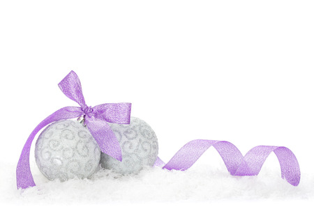 Christmas baubles and purple ribbon over snow. Isolated on white background with copy space