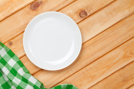 Empty plate and towel over wooden table background. View from above with copy space photo