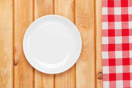 red tablecloth: Empty plate and towel over wooden table background. View from above with copy space