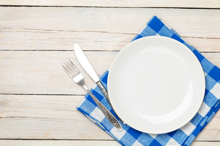 Empty plate, silverware and towel over wooden table background. View from above with copy space Reklamní fotografie