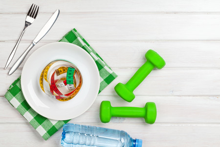 bodies of water: Dumbells and healthy food over wooden background. View from above with copy space