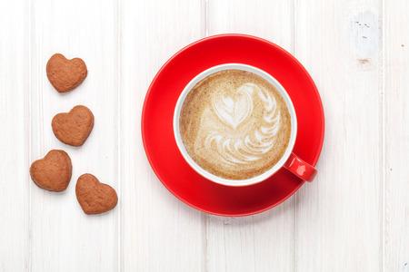 발렌타인 데이 하트 모양의 쿠키와 빨간 커피 컵입니다. 흰색 나무 테이블 위에서 볼