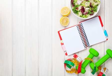 Dumbells, tape measure, healthy food and notepad for copy space. Fitness and health photo
