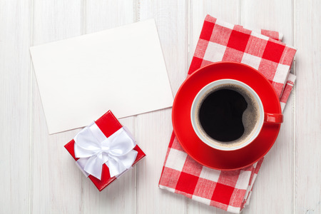 Valentines day greeting card, gift box and coffee cup over white wooden table photo