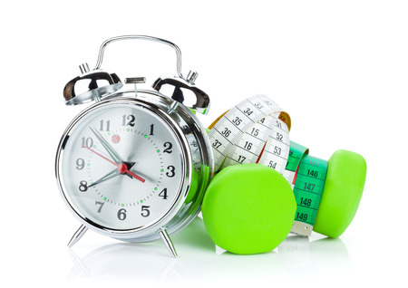 Two green dumbells, tape measure and alarm clock. Fitness and health. Isolated on white background photo