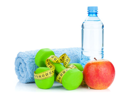 heavy weight: Two green dumbells, tape measure, apple and water bottle. Fitness and health. Isolated on white background
