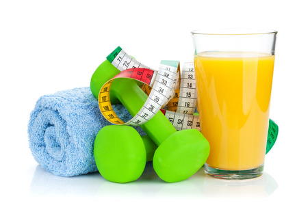 Two green dumbells, tape measure and orange juice. Fitness and health. Isolated on white background photo