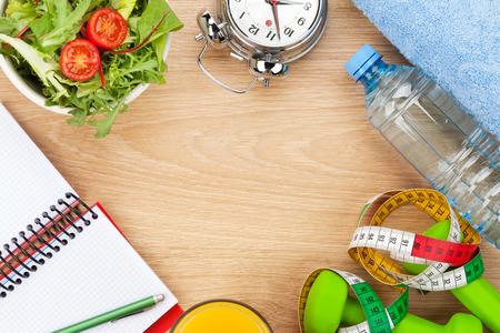 Dumbells, Maßband und gesundes Essen über Holzuntergrund. Fitness und Gesundheit. Blick von oben mit Kopie Raum Standard-Bild