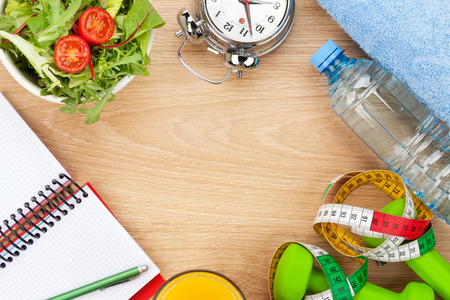 Dumbells, tape measure and healthy food over wooden background. Fitness and health. View from above with copy space photo
