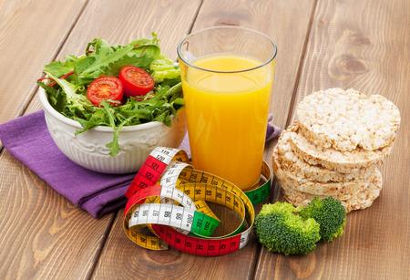 La comida sana y cinta métrica sobre mesa de madera. Fitness y salud