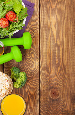 wooden background: Dumbells, tape measure and healthy food over wooden background. Fitness and health. View from above Stock Photo