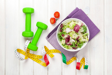 Dumbells, tape measure and healthy food. Fitness and health Stock Photo