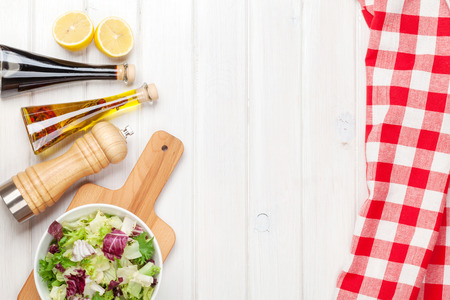Fresh healthy salad and condiments over white wooden table. View from above with copy space photo