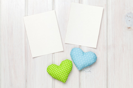 Photo frames and valentines toy hearts over wooden table background