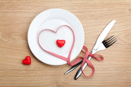 diet dinner: Valentines Day heart shaped red ribbon over plate with silverware. On wooden table background