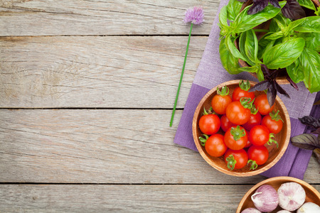 rustic food: Fresh farmers tomatoes and basil on wood table. View from above with copy space Stock Photo