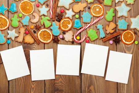 five years old: Christmas wooden background with photo frames, candies, spices and gingerbread cookies