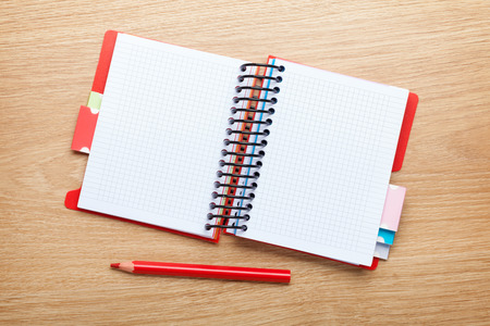 Office table with blank notepad and red pencil. View from above with copy space