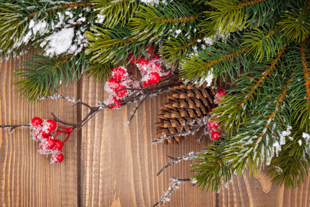 Christmas wooden background with snow fir tree and holly berry photo