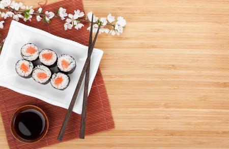 Sushi maki met zalm en sakura tak over bamboe tafel