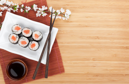Sushi maki with salmon and sakura branch over bamboo table Stock Photo