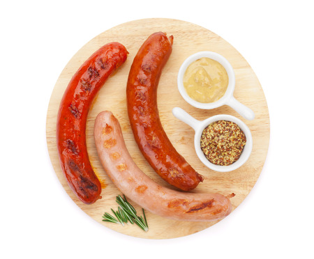 Various grilled sausages with condiments on cutting board. Isolated on white background photo