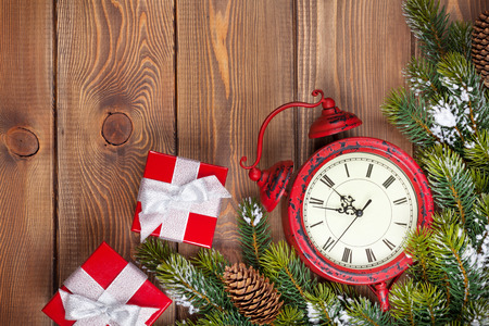 twelve month old: Christmas wooden background with clock, gift boxes, snow fir tree and copy space