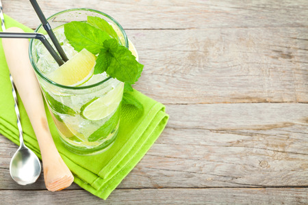 Fresh mojito cocktail and bar utensils on wooden table with copy space Stock Photo