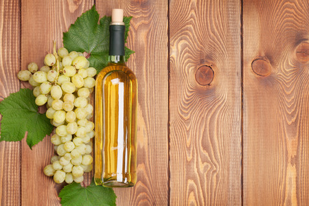 white wine bottle: White wine bottle and bunch of white grapes on wooden table background with copy space