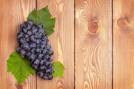 grapes: Racimo de uvas rojas en el fondo de la tabla de madera con espacio de copia