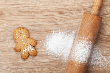 Rolling pin with flour and gingerbread cookie on wooden table. View from above photo