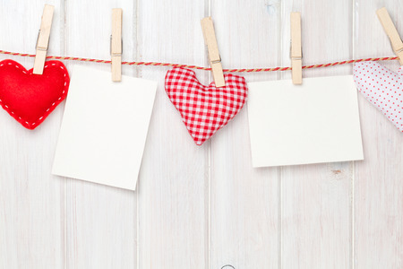 Photo frames and valentines toy hearts over wooden background photo