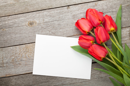 Fresh tulips and greeting card over wooden table background photo