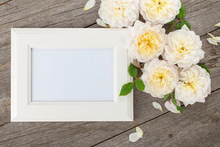 木製のテーブル背景に空白のフォト フレームと白バラ