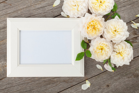 pictures: Blank photo frame and white roses over wooden table background