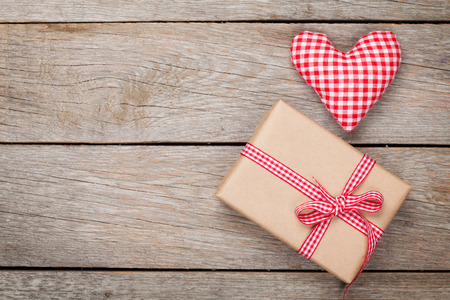 Valentines day toy heart and gift box over wooden table background photo