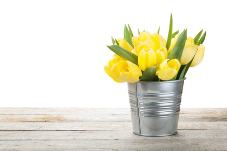 Fresh yellow tulips bouquet over wooden table. Isolated on white background photo
