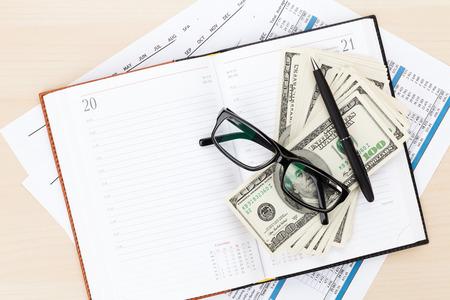 cuadro sinoptico: Escritorio de oficina con los informes, la libreta en blanco y dinero en efectivo. Vista desde arriba, con copia espacio
