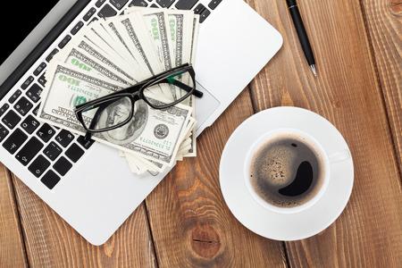 オフィスの pc、コーヒー カップ、グラス、お金を現金でテーブル。上からの眺め