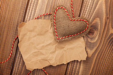 Blank old piece of paper and vintage handmaded valentines day toy heart over wooden background photo