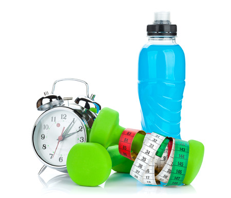 energy drinks: Two green dumbells, tape measure, drink bottle and alarm clock. Fitness and health. Isolated on white background