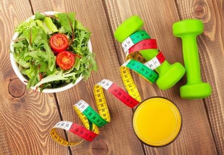 ensalada tomate: Dumbells, cinta m�trica y alimentos saludables sobre la mesa de madera. Fitness y salud. Vista desde arriba Foto de archivo