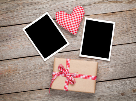 Valentines day toy heart, blank photo frames and gift box over wooden table background