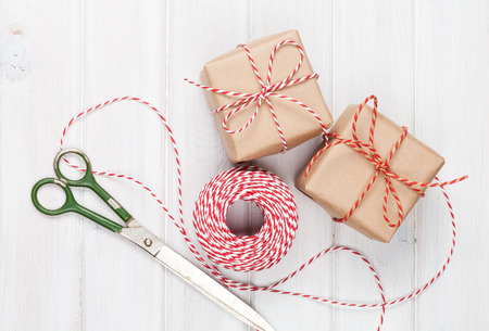 scissors: Gift wrapping with boxes and scissors over white wooden table Stock Photo