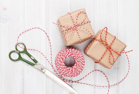 tijeras: Papel de regalo con las cajas y tijeras sobre la mesa de madera blanca Foto de archivo