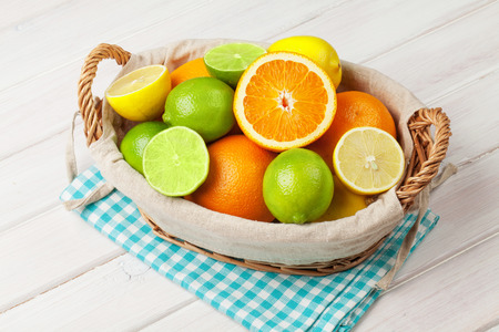 Citrus fruits in basket. Oranges, limes and lemons. Over white wood table background photo