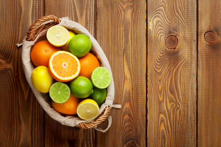 mandarin orange: Citrus fruits in basket. Oranges, limes and lemons. Over wood table background with copy space