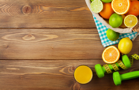 rustic food: Citrus fruits in basket and dumbells. Oranges, limes and lemons. Over wood table background with copy space