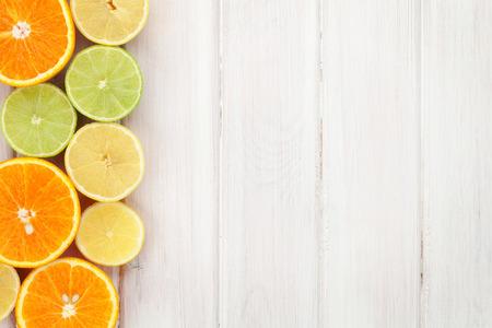 Citrus vruchten. Sinaasappels, limoenen en citroenen. Over houten tafel achtergrond met kopie ruimte Stockfoto