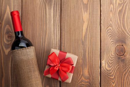 Rode wijnfles en de doos van de gift van de dag van Valentijnskaarten. Over rustieke houten tafel achtergrond met kopie ruimte Stockfoto